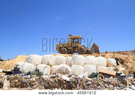 Bulldozer in public landfill over garbage dump