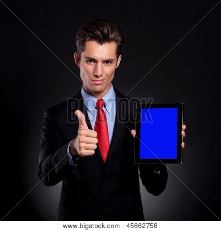 portrait of a young business man standing against a black background presenting a tablet and showing thumbs up sign while smiling to the camera