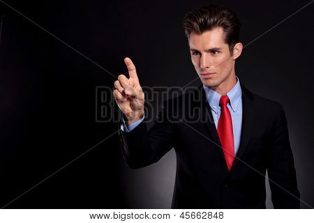 portrait of a young business man standing against a black background and selecting something from an imaginary screen with his finger while looking at it very focused