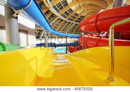 Big multi-colored indoor water slides in aquapark. Descent yellow slide.