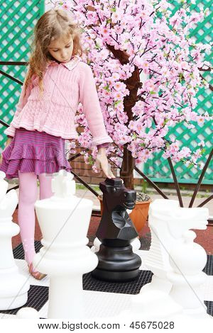 Girl next to artificial cherry blossom touches big chess pieces on big chessboard in park. Focus on tree.