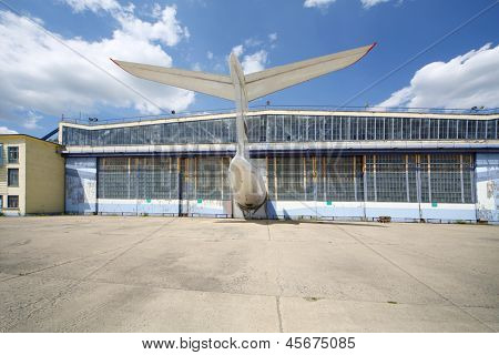 Big old battered aircraft hanger with protruding tail of plane at sunny summer day.