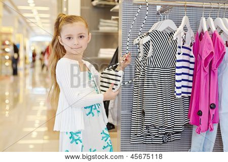 Little girl stands holding stylish striped female handbag