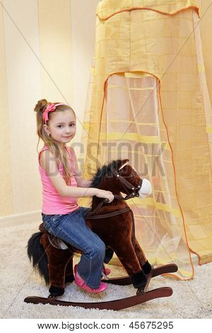 Little girl rocks on rocking horse in play room