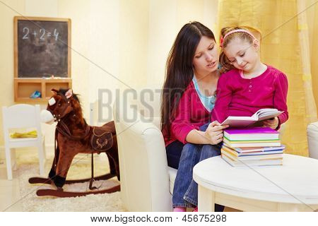 Mother reads book to her daughter sitting in armchair in playroom