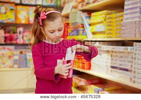 Little girl views box with envelopes in book department of store
