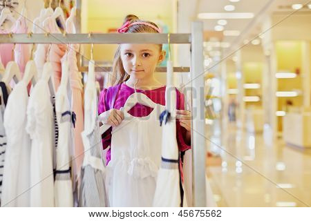 Little girl with rucksack on shoulders holds hander with white gown in clothing store