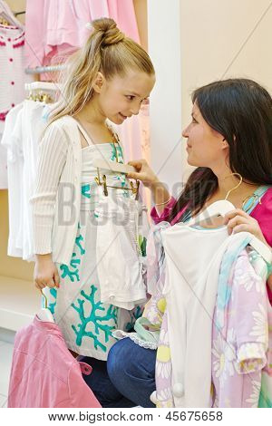 Mother and daughter try on clothes in clothing store