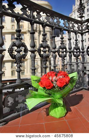 Bouquet of red roses stands on beautiful balcony in sunny day.