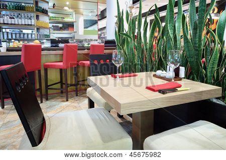Quadratischer Tisch mit Brille und Bar im Saal des gemütlichen japanisches Restaurant.