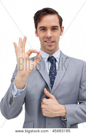 Smiling businessman showing ok sign against white background