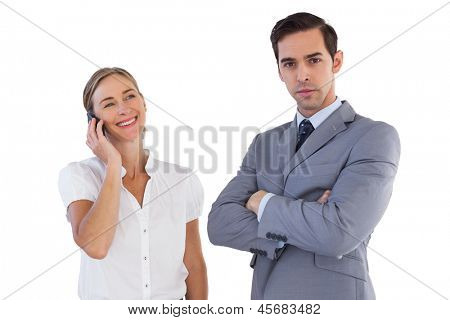 Smiling businesswoman on the phone next to her colleague on white background
