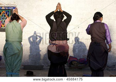 LHASA, TIBET-OCTOBER 08: Female Tibetan buddhist pilgrims are praying in front of Jokhang Temple on October 08, 2012 in Lhasa, Tibet.