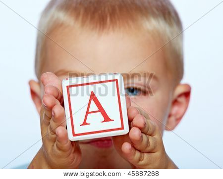 little 3 year old toddler boy playing with wooden abc alphabet blocks on studio background