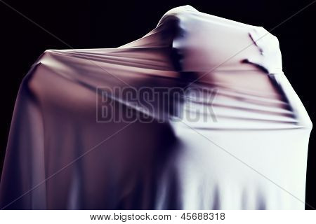 Art photo of a women silhouette breaking through the fabric. Struggle concept.