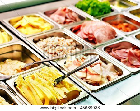 Tray with cooked food on showcase at cafeteria.