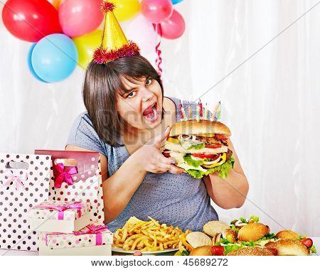 Woman eating hamburger at birthday. Isolated.