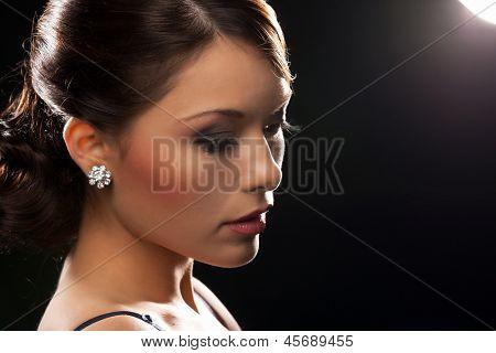 mulher bonita em vestido de noite usando brincos de diamante