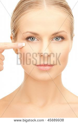 face of beautiful woman touching her eye area