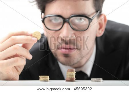 young businessman with glasses counting coins