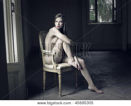 hermosa mujer desnuda en una silla antigua