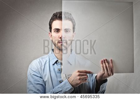 young man holds transparent panel in front of his face