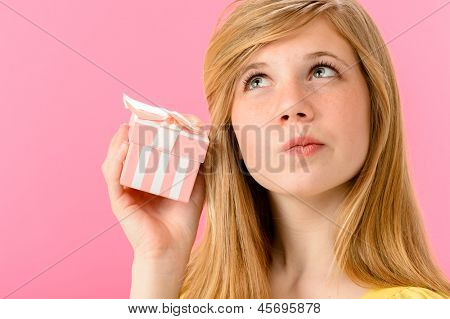 Curious girl holding unopened present isolated on pink background