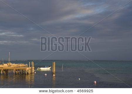 Small Boat And Pier With Cloudy Horizon