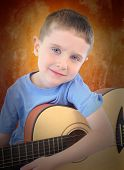 Young Boy Holding Acoustic Guitar