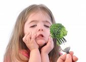 foto of reject  - A young girl is making a funny disgusting face at a fork with a healthy piece of broccoli on a white background - JPG