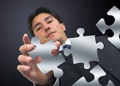 foto of peculiar  - business man arranging puzzle pieces - JPG
