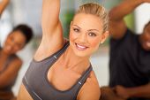 stock photo of stretch  - beautiful fit woman stretching in gym with friends - JPG