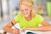 stock photo of preteen  - happy preteen girl writing homework at home - JPG