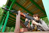 stock photo of sniper  - Young woman aiming at a target and shooting an automatic rifle for strikeball - JPG