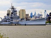 foto of battleship  - Battleship docked on the Delaware River with Philadelphia skyline in the background - JPG
