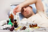 stock photo of inhalant  - Adult man patient with high temperature lying down bed for cold and flu illness relief - JPG
