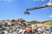 stock photo of landfills  - Grabber crane working over pile of domestic garbage - JPG