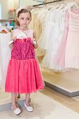 Beautiful girl tries on a bright red dress in the modern store childrens clothes