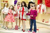 Little girl in dark sunglasses stands together with group of dressed mannequins and performs one of