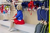 Sitting female fashion doll in clothing store
