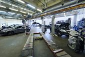 Many cars stand in car garage with special equipment for repair.