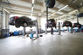 stock photo of motor vehicles  - Four black cars on lifts in small service station and two men repair one car - JPG