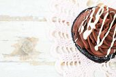 Chocolate cupcake with butter cream icing on grunge wooden background with copy space