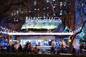 NEW YORK CITY - APRIL 15: Customers dine at Shake Shack in Madison Square Park April 15, 2013 in New
