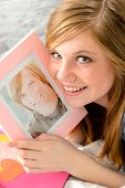 Smiling teenage girl holding a picture of her love