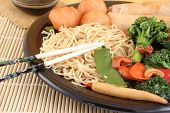 picture of lo mein  - delicious chinese lo mein noodles and stir fry vegetables with cashews with chicken balls spring rolls soya sauce and chopsticks on a bamboo placemat - JPG