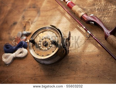 Vintage fishing reel, and rod on old wooden surface.