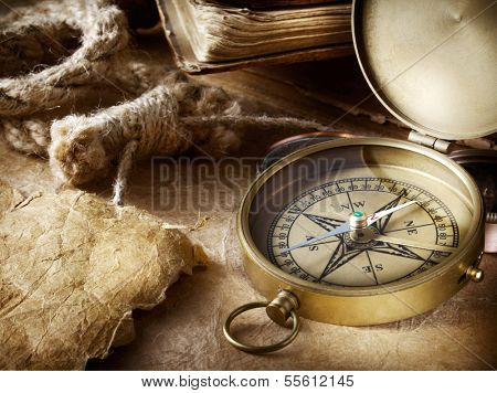 Vintage compass, old books, parchment