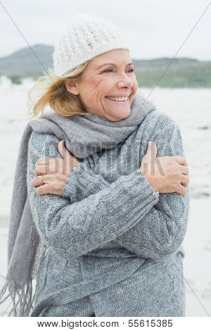 Cheerful senior woman shivering as she looks away at the beach