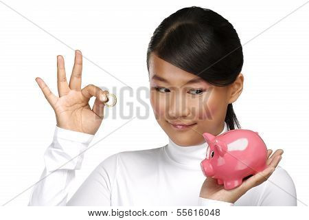 Beautiful Happy Chinese Girl Showing A Piggybank